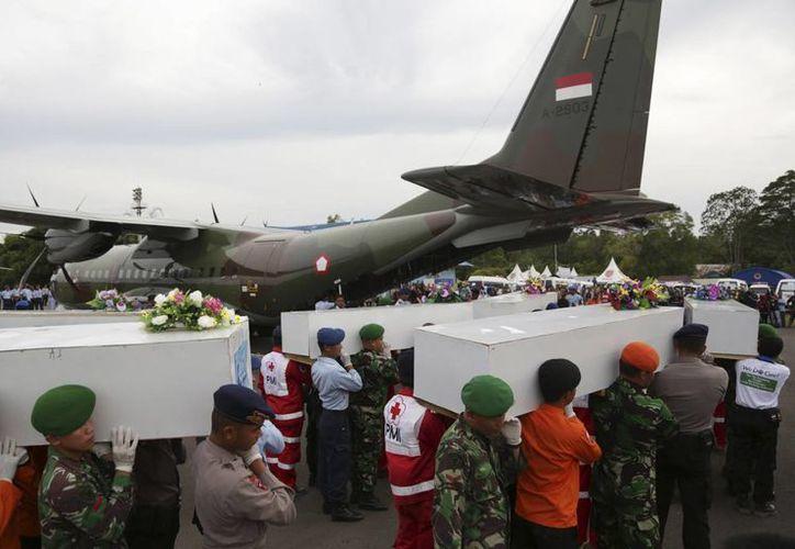 Rescatistas cargan los ataúdes de los pasajeros que perdieron la vida en el accidente aéreo del vuelo de AirAsia, en el aeropuerto de Pangkalan Bollo, Indonesia. (Agencias)