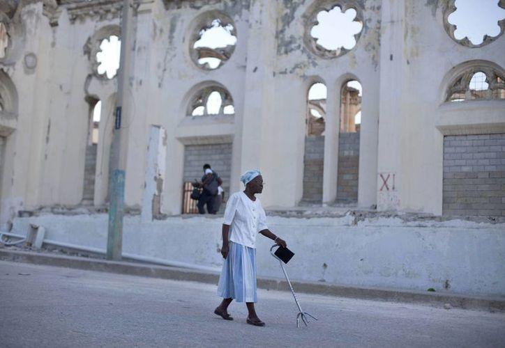 Una mujer pasa junto a las ruinas de la catedral nacional durante el quinto aniversario del terremoto de enero de 2010 en Port-au-Prince, Haití. (Agencias)