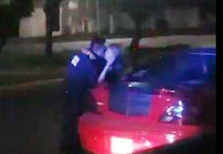 Imagen del video donde se ve a un policía uniformado besando a una mujer que conducía el vehículo rojo. (Captura de pantalla/Twitter @Yoali_GM)