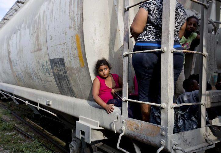 Una niña inmigrante y su familia esperan que el tren de carga salga de Ixtepec, Oxaca, hacía la frontera con EU. (Agencias)