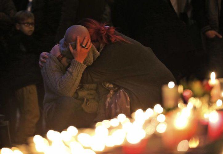 Dos personas se abrazan ante la ofrenda a las víctimas de uno de los atentados ocurridos en Francia. (Agencias)