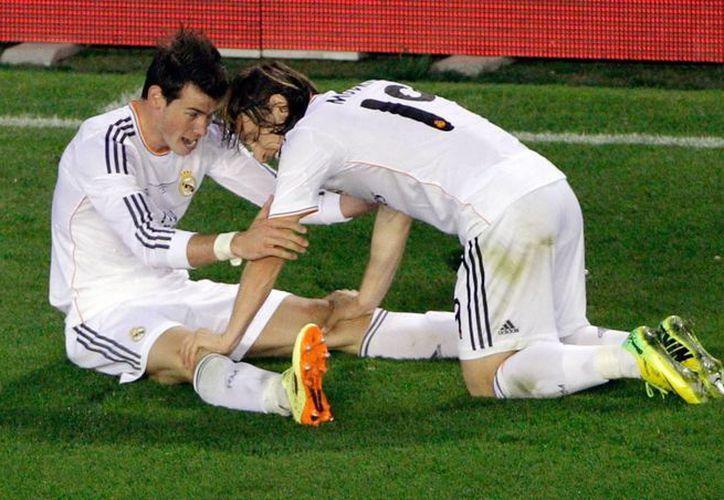 El centrocampista croata del Real Madrid Luka Modric (d) felicita al galés Gareth Bale, tras la anotación de un gol. (EFE/Foto de archivo)