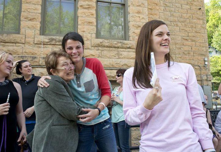 Jennifer Rambo (der), sonríe mientras su compañera Kristin Seaton (c), abraza a Sheryl Maples, la abogada que pedía eliminar la prohibición de las bodas homosexuales. (Agencias)