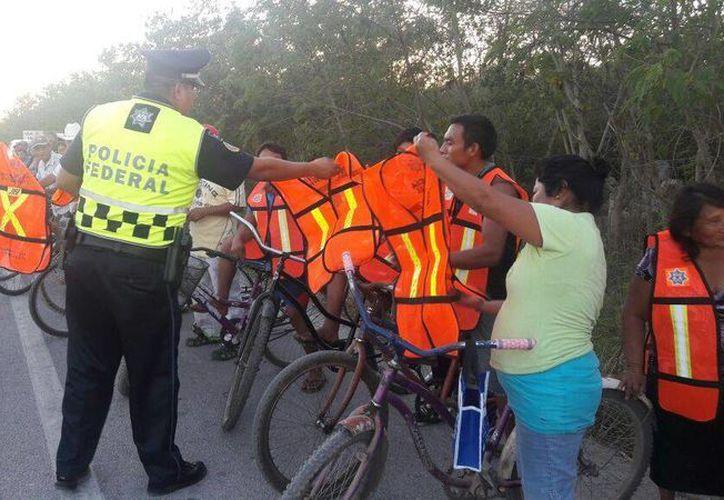La Policía Federal con apoyo de empresas socialmente responsables entregó chalecos y brindó pláticas de seguridad vial a ciclistas en la vía Mérida Tizimín. (Luis Fuente/SIPSE)