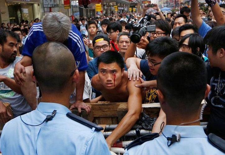 Taxistas y manifestantes chocaron este miércoles en Hong Kong. Los transportistas intentaban quitar las barricadas que los inconformes colocaron como forma de protesta en  varias calles de la ciudad. (AP)