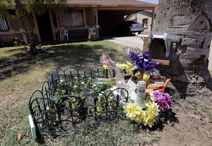 Monumento conmemorativo afuera de la casa donde un presunto asesino serial asesinó a un hombre anteriormente en el año en Phoenix. Las autoridades han dado a conocer reportes policiales sobre dos de siete muertes a balazos que las autoridades creen fueron efectuadas por un asesino serial. (AP/Matt York)