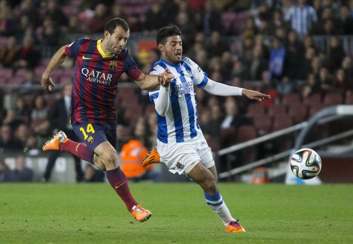 Carlos Vela (de blanco y azul) dice que a él el futbol no le apasiona, pero sí le encanta. (Foto de archivo de Notimex)