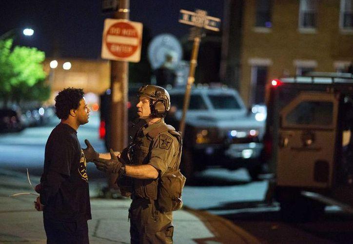 Un hombre es detenido por violar el toque de queda este martes en Baltimore. Un grupo de policías antidisturbios lanzó granadas de humo y disparó pelotas de pimienta a decenas de manifestantes para imponer un toque de queda en toda la ciudad. (AP Photo/David Goldman)