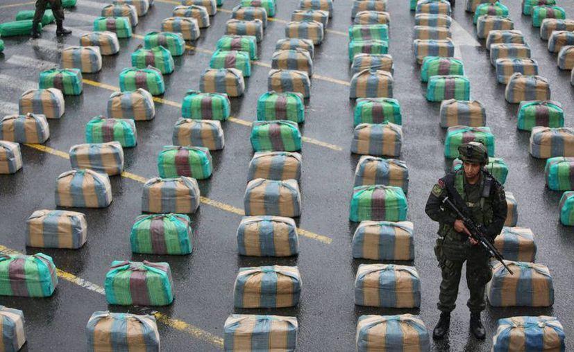 Un integrante de la policía de Colombia custodia un decomiso de toneladas de marihuana. (EFE)