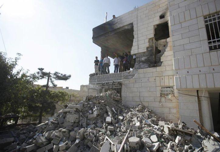 Varias personas recorren la vivienda de Amer Abu Aisheh, uno de tres palestinos identificados por Israel como sospechosos de la muerte de tres adolescentes israelíes, un día después de su demolición por el ejército en Hebrón, Cisjordania, el lunes 18 de agosto de 2014. (Agencias)