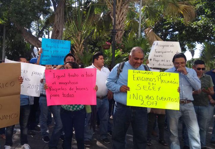 Con pancartas y consignas, alrededor de 50 maestros protestaron la mañana de este sábado frente al Palacio de Gobierno. (Foto Óscar Chan)