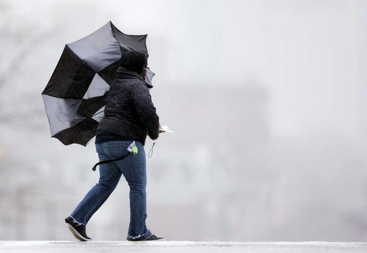 A pesar del mal tiempo, una mujer avanza entre las calles en Filadelfia. (Foto: AP)