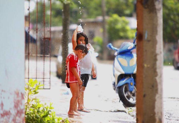 "A pesar del ""fresco"", algunos niños disfrutaron de la lluvia vespertina, en Mérida. (Juan C. Albornoz/SIPSE)"