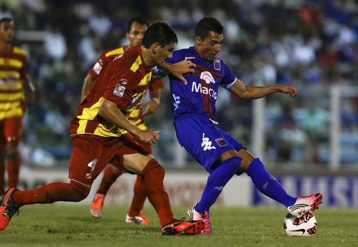 Ruben Botta de Tigre, derecha, disputa un balón a Javier López, del Deportivo Anzoátegui. (Agencias)