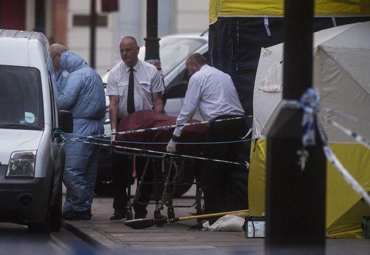 Investigadores retiran un cuerpo en la escena donde una mujer murió y varias personas resultaron heridas por un sospechoso ataque con cuchillo hoy, jueves 4 de agosto. (EFE)