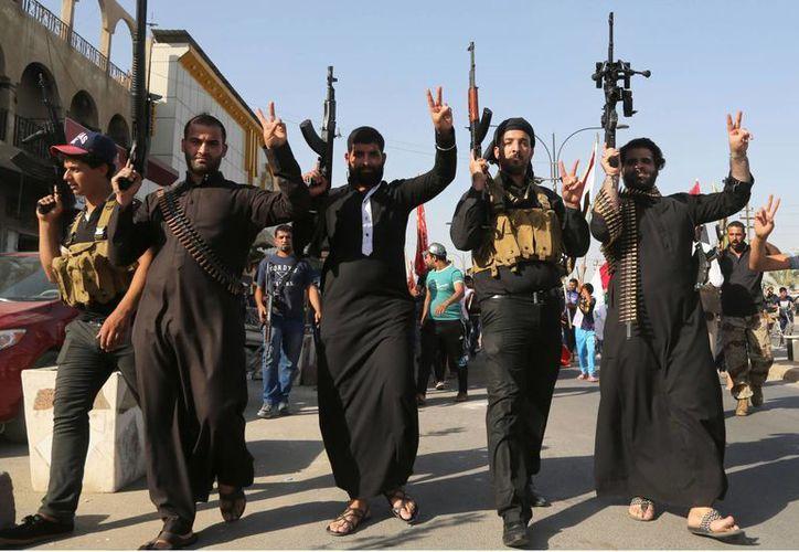 Combatientes chiítas levantan sus armas y corean consignas contra el Estado islámico en Irak.(Archivo/AP)