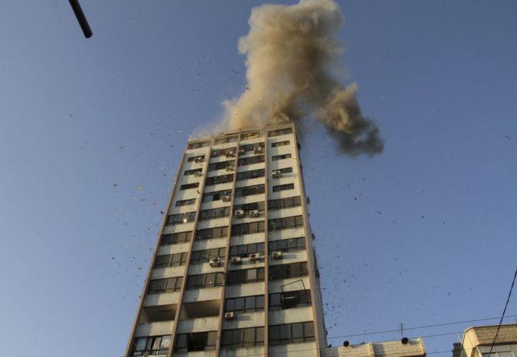 Una columna de humo asciende luego de la explosión en la sede de la televisora local Al-Aqsa en Ciudad de Gaza. (Agencias)