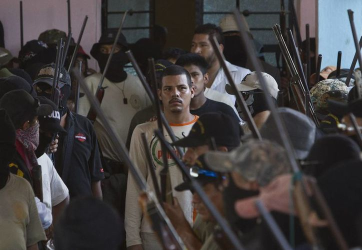 Miembros enmascarados de la comunidad de Ayutla escoltan a unos de los detenidos a una asamblea comunitaria en la localidad de El Meson. (Agencias)
