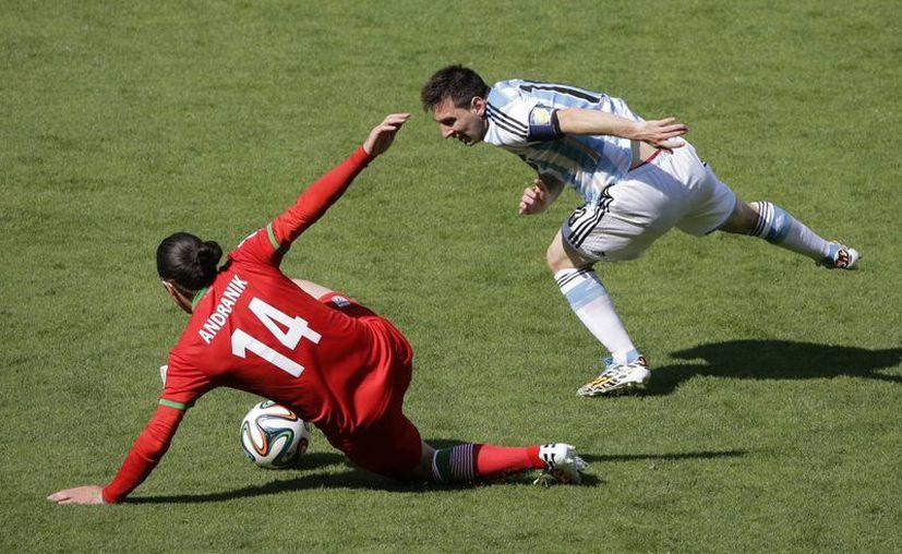 El iraní  Andranik Teymourian despeja ante el acoso del artillero argentino Lionel Messi. (Fotos: AP)