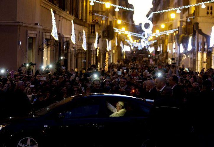 El Papa Francisco saluda a los fieles al retornar a bordo de su automóvil al Vaticano, luego de rezar ante la imagen de la Virgen en la Plaza España de Roma. (Foto: AP)
