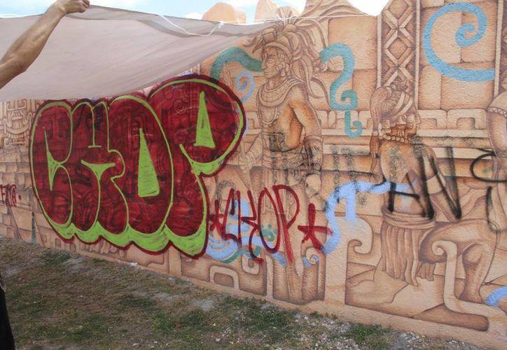 El mural fue grafiteado, por lo que se les colocó una manta blanca para cubrir las partes alteradas. (Tomás Álvarez/SIPSE)