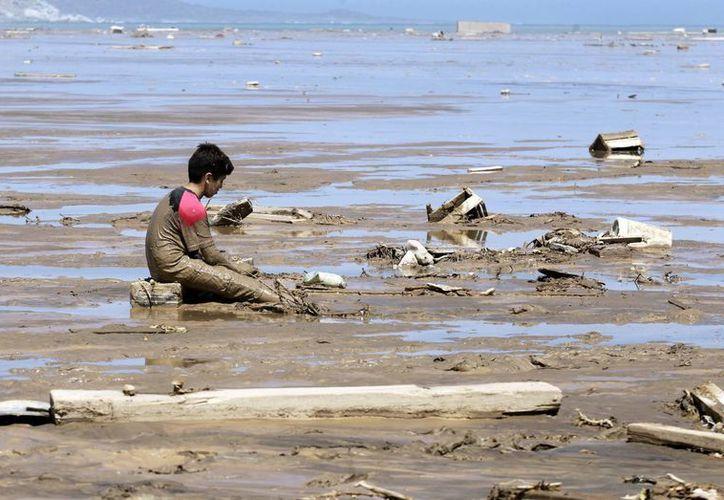Un niño permanece sentado en la playa de la localidad de Charañal, tras las inundaciones torrenciales en esa localidad a 1000 kilómetros al norte de Santiago de Chile. (Archivo/EFE)