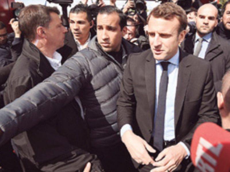 In this file photo French centrist presidential election candidate Emmanuel Macron, flanked by his bodyguard, Alexandre Benalla, left, in Amiens, northern France.