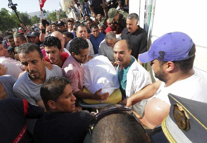 Varios médicos tunecinos cargan el cuerpo del opositor político Mohamed Brahmi, mientras un grupo de protestantes se junta en las inmediaciones del hospital. (EFE)