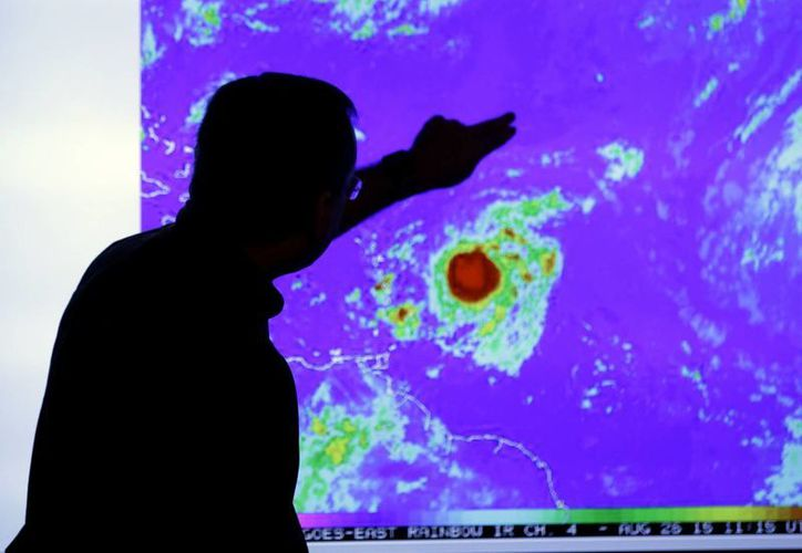 El meteorólogo James Franklin observa una imagen de la tormenta tropical Erika conforme se mueve al oeste hacia islas en la parte oriental del Caribe, el miércoles 26 de agosto de 2015, en el Centro Nacional de Huracanes, en Miami. (Foto AP/Lynne Sladky)