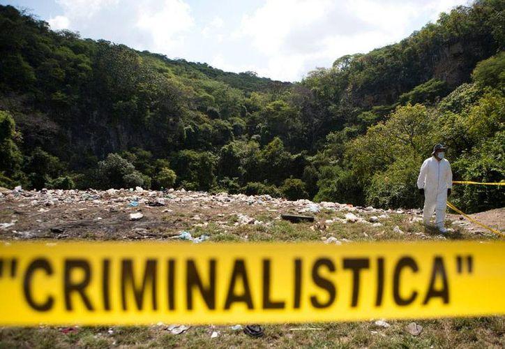 Con trajes asépticos blancos, peritos forenses revisaron superficialmente un terreno en Cocula, donde se presume hay restos humanos. La PGR no ha dado información oficial al respecto. (AP)