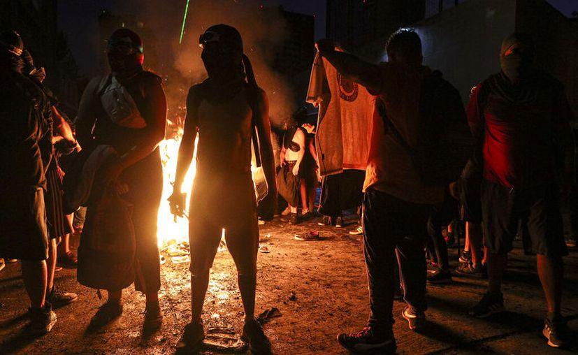 Manifestantes contra el gobierno empapados por un cañón hidrante de la policía se secan junto a una barricada en llamas en Santiago de Chile. (AP Photo/Esteban Felix)
