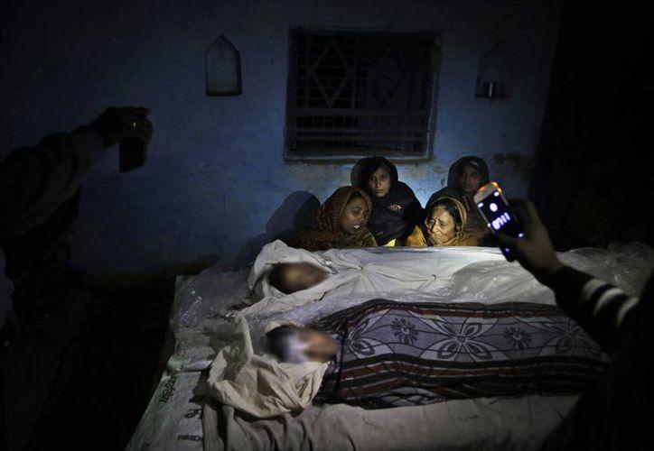 Una madre, izquierda, llora al lado de los cadáveres de sus hijas, quienes murieron en el accidente que se registró en la villa de Ramnagar, cerca de Etah, en India. (AP/Altaf Qadri)
