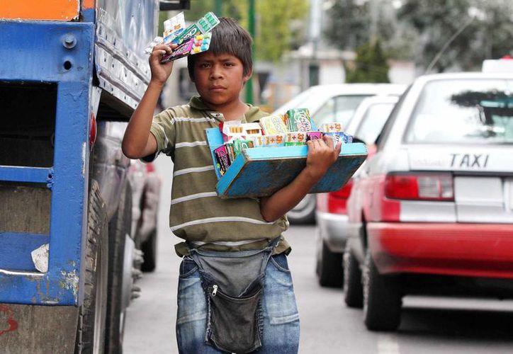 El representante de Unicef dijo que uno de los retos de México son los tres millones de menores de entre cero y 17 años que no asisten a la escuela. Foto de contexto de un menor vendiendo artículos en la ciudad de México. (Archivo/Notimex)