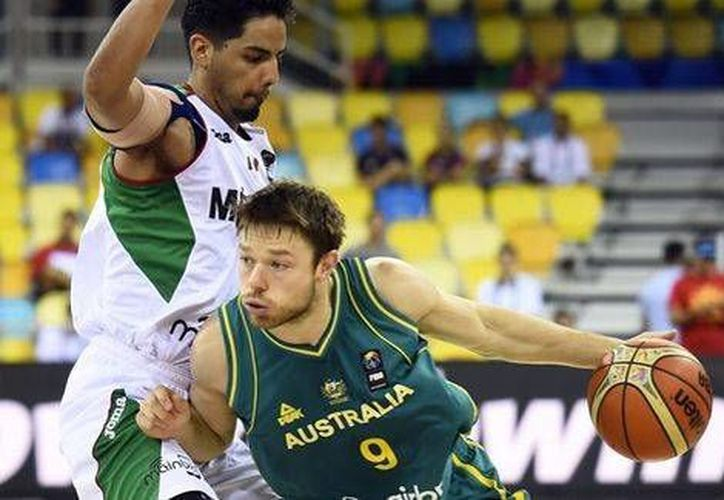 Jorge Gutiérrez (izq) intenta detener a un jugador australiano. (AFP/Milenio)