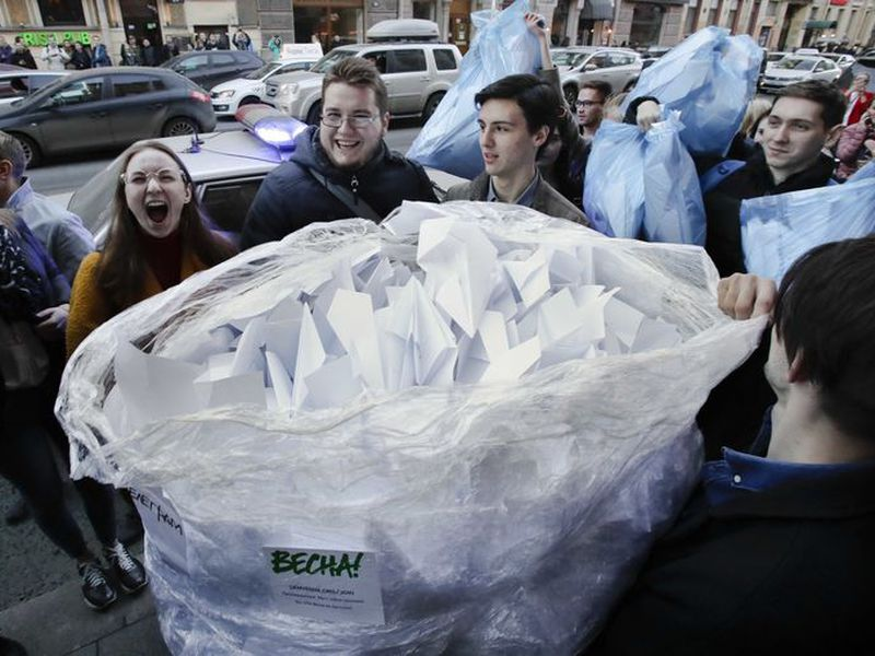 Activists bring a sack with about 2,000 paper airplanes symbolising the logo of the messaging app Telegram to the door of St. Petersburg's department of Roskomnadzor, in St. Petersburg, Russia. (AP)