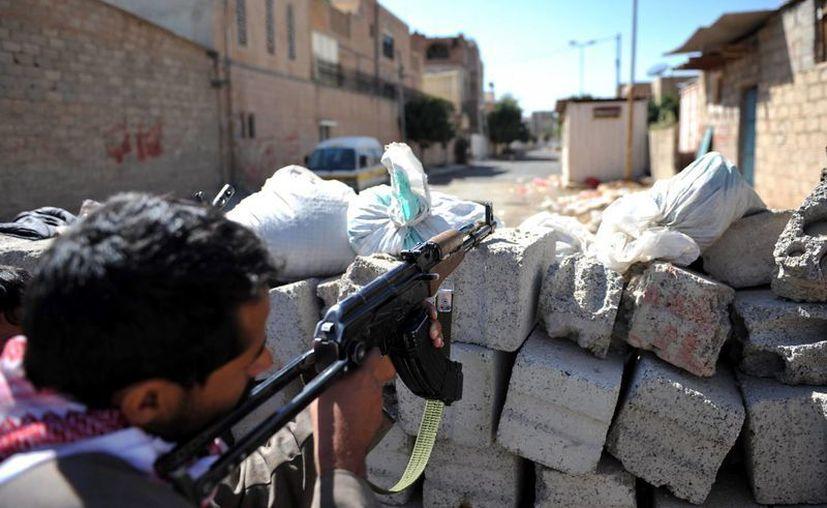 Un miliciano de los líderes tribales opositores apunta con su Kalashnikov desde una barricada montada en una calle de Saná, en el Yemen. (EFE)
