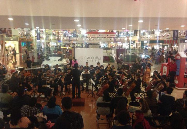 Gente que realizaba sus compras se acercó a disfrutar el recital que ofreció la Sinfónica Infantil y Juvenil. (Milenio Novedades)