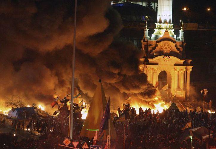 Vista del humo que proviene de la quema de neumáticos en la Plaza de la Independencia, donde continúan las protestas sin tregua, en Kiev. (EFE)