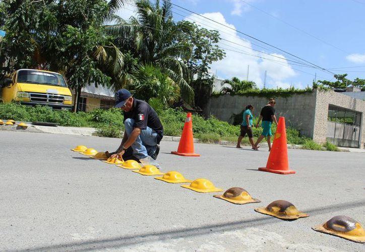 Personal de la Dirección de Tránsito instaló boyas en la calle Sagitario.  (Sara Cauich/SIPSE)