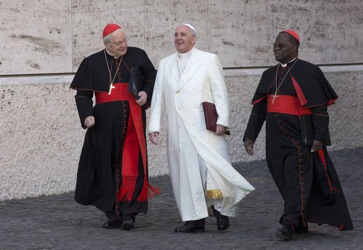 Papa Francisco, flanqueado por los cardenales Angelo Sodano, (izq), y Laurent Monsengwo Pasinya, llegando a una sesión en el Aula del Sínodo en el Vaticano. (Agencias)