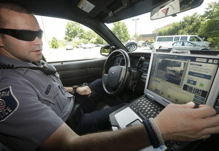 El oficial Dennis Vafier, del Departamento de Policía de Alexandría, Virginia, utiliza una computadora enlazada a su cuartel, con el que puede escanear las placas de automotores. (AP)