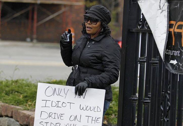 Shena Hardin caminó con un letrero en Cleveland, en cumplimiento de un castigo muy difundido por haber rebasado por la acera a un autobús escolar.(Fotos: Agencias)