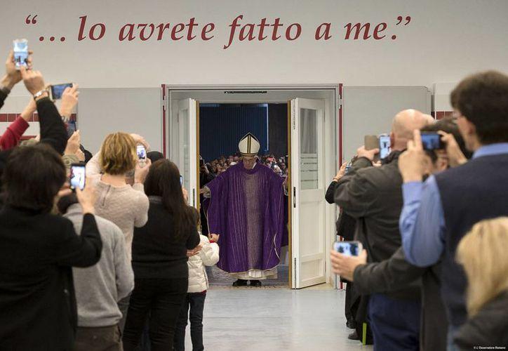 El papa Francisco abrió una simple puerta de vidrio de un comedor de Cáritas en Roma y se dio tiempo para saludar y bendecir a los presentes. (AP)