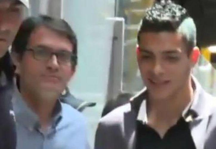 Raúl Jiménez (segundo desde la derecha) se tomó fotos con aficionados del Atlético de Madrid a su llegada al aeropuerto español. (Captura de pantalla de YouTube)