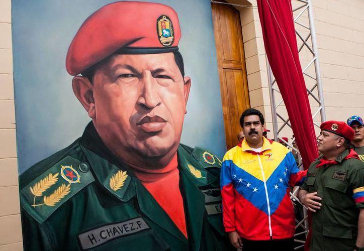 El vicepresidente de Venezuela, Nicolás Maduro (c), y el presidente del Congreso Nacional venezolano, Diosdado Cabello, frente a una pintura gigante del rostro del presidente de Venezuela, Hugo Chávez. (EFE)