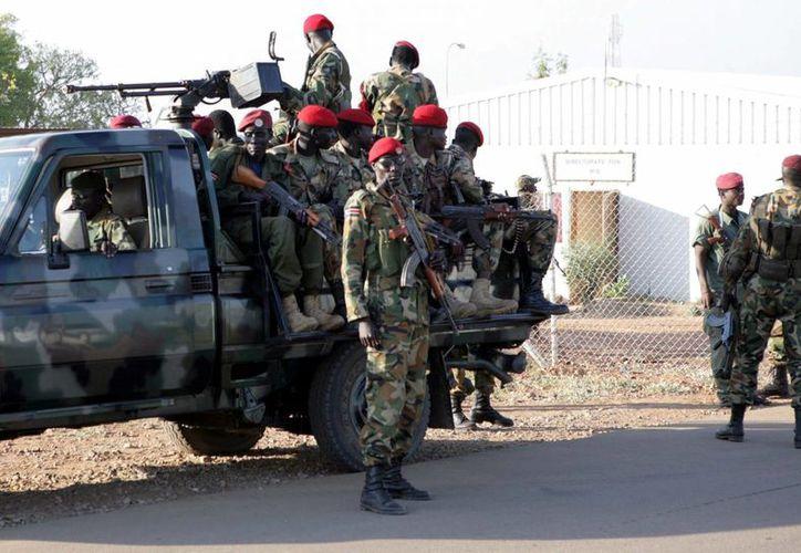 Numerosos soldados sursudaneses patrullan una calle en Juba. Al parecer de nada sirvió que el gobierno aceptara poner fin a las hostilidades contra rebeldes que controlan algunas partes del país. (EFE)