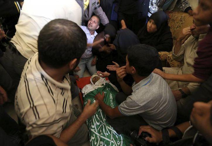 Palestinos lloran ante el cadáver de un militante de Hamás durante su funeral en Jan Yunes, al sur de la franja de Gaza. (EFE)