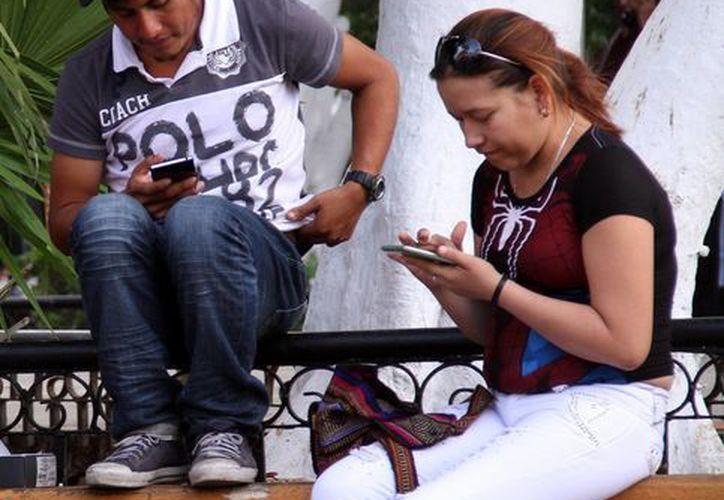 Para acceder al Congreso Virtual Internacional de Innovación, Vinculación y Educación Superior, puede puede ser desde cualquier dispositivo. Foto de un par de jóvenes que usan su celular en el Plaza Grande de Mérida. (Milenio Novedades)