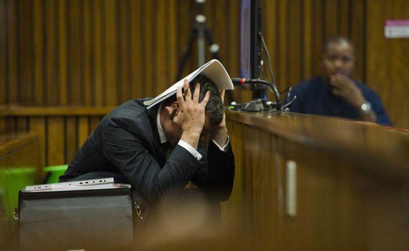 Pistorius se cubre la cabeza con una libreta mientras escucha evidencia de un investigador forense en el juicio por el asesinato de su novia. (Agencias)