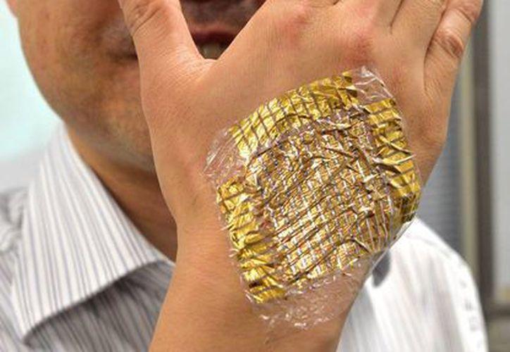 El profesor Takao Someya muestra cómo funciona el chip.(Agencias)